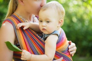 51153313 - baby in sling outdoor. mother is carrying her child and showing nature details